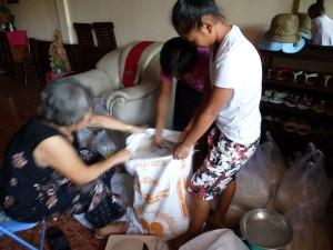 Ma mère et nos deux petites mains pèsent le riz, plus pour les familles nombreuses et moins pour les autres