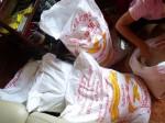 Deux personnes sont venues à la rescousse pour peser le riz afin de distribuer équitablement