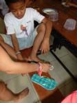 Une distribution de chaussures-tongs pour les enfants